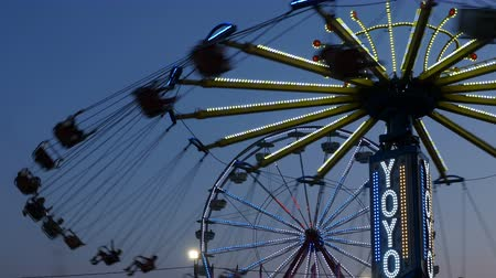 augusta : AUGUSTA, NJ - AUGUST 6: The colorfully illuminated Yo-Yo spins in front of the Gentle Giant Ferris Wheel at twilight sky during the New Jersey State Fair on August 6, 2014 at the Sussex County Fairgrounds in Augusta, New Jersey.
