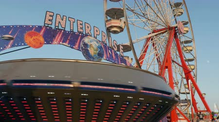augusta : AUGUSTA, NJ - AUGUST 7: The colorfully illuminated Enterprise spins in front of the Gentle Giant Ferris Wheel during the New Jersey State Fair on August 7, 2014 at the Sussex County Fairgrounds in Augusta, New Jersey. Stock Footage