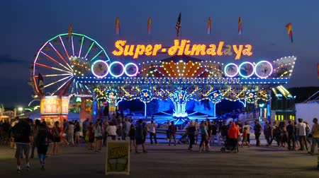 augusta : AUGUSTA, NJ - AUGUST 7: The colorfully illuminated Super-Himalaya ride spins with the Gentle Giant Ferris Wheel in the background at twilight sky during the New Jersey State Fair on August 7, 2014 at the Sussex County Fairgrounds in Augusta, New Jersey.