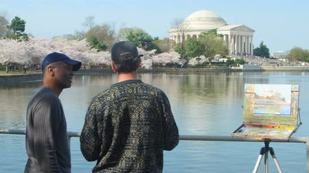 şövale : WASHINGTON - APRIL 13: Two artists talk in front of an in-progress painting of the Jefferson Memorial and cherry blossoms around Tidal Basin on April 13, 2015 in Washington.