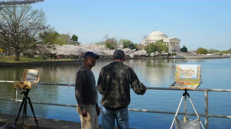 şövale : WASHINGTON - APRIL 13: Two artists talk in front of an in-progress paintings of the Jefferson Memorial and cherry blossoms around Tidal Basin on April 13, 2015 in Washington.