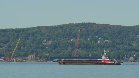 pozisyon : TARRYTOWN, NY - SEPTEMBER 15: A Weeks tugboat moves a barge into position for work on construction of the New Tappan Zee Bridge over the Hudson River between Westchester and Rockland counties on September 15, 2015 in Tarrytown. Stok Video