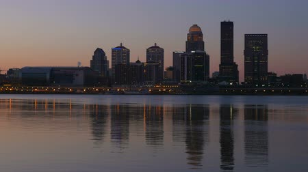 západ : The illuminated skyline of Louisville, Kentucky is reflected in the waters of the Ohio River as the sky lightens during morning twilight.