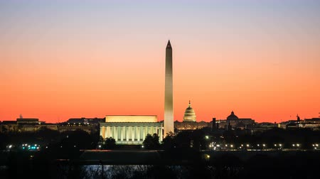 (Time-lapse) National Mall attractions including the Lincoln Memorial, Washington Monument and US Capitol building are illuminated as the orange pre-sunrise sky begins to lighten in Washington, DC.