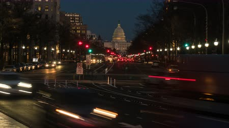 (Time-lapse) Traffic moves on Pennsylvania Avenue, with the US Capitol building in the background, during evening twilight in Washington, DC.