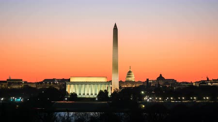 (Time-lapseZoom-in) National Mall attractions including the Lincoln Memorial, Washington Monument and US Capitol building are illuminated as the orange pre-sunrise sky begins to lighten in Washington, DC.