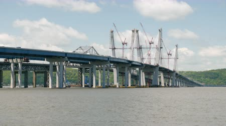 The new Tappan Zee cable-stayed bridge under construction over the Hudson River under a partly cloudy sky in Tarrytown, New York. Stock Footage