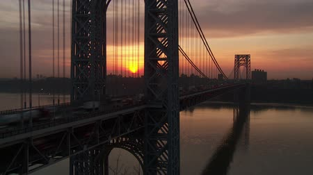 fort lee : (Time-lapse) The sun rises while morning rush hour traffic on the George Washington Bridge crosses the Hudson River between New Jersey and New York.