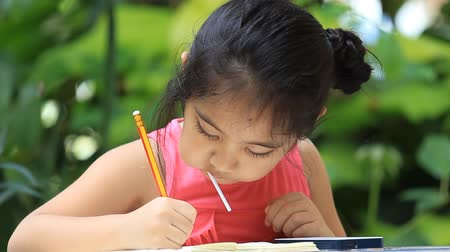 vonalvezetés : Little Asian girl drawing picture and eating candy
