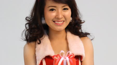 подарок : Pretty Asian woman on santa dress giving a present Стоковые видеозаписи