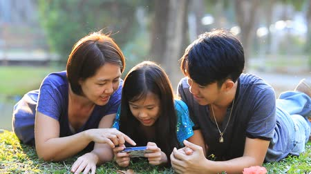asian family : Happy Asian family playing a game on smart phone together in park Stock Footage