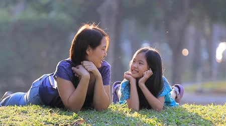 японский : Happy Asian mother and daughter on grass at sunny summer day in park, tilt up camera