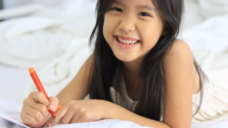комфорт : Little Asian girl laying down and drawing on the bed Стоковые видеозаписи