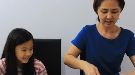 culinária : Asian daughter helping mother to slice up vegetables in kitchen