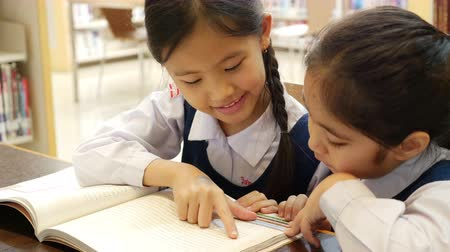 olvasás : 4K UHD : Little Asian students with uniform reading book in library together