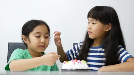 morder : Happy Asian girls having fun with cream from birthday cake