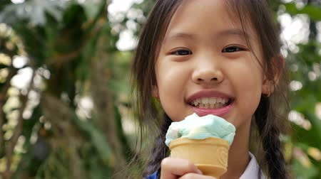 капелька : 4K Video of little Asian girl enjoying her ice cream