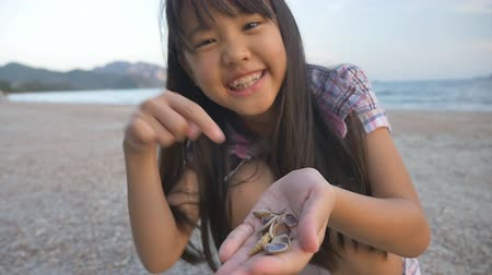 оболочка : Little Asian child picking shells on the beach