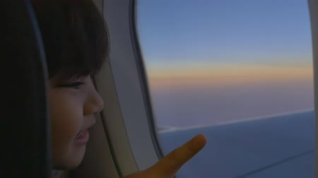 идущий : Happy little Asian girl looking outside the window of airplane Стоковые видеозаписи