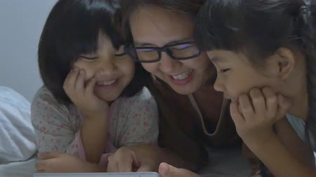 время ложиться спать : Asian mom lies with her daughters and plays with digital tablet together, Pan shot