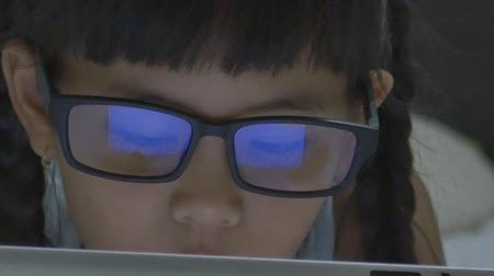 reflexão : Close up of Asian child using tablet computer with reflection in glasses, Pan shot
