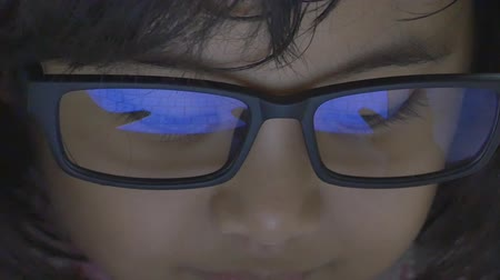 yansıma : Close up of Asian child using tablet computer with reflection in glasses, Tilt up shot