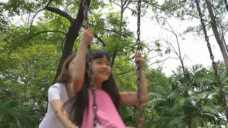 наслаждаться : Slow motion of little Asian girl playing on swing set with mother in playground Стоковые видеозаписи