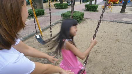 etkinlik : Slow motion of little Asian girl playing on swing set with mother in playground Stok Video