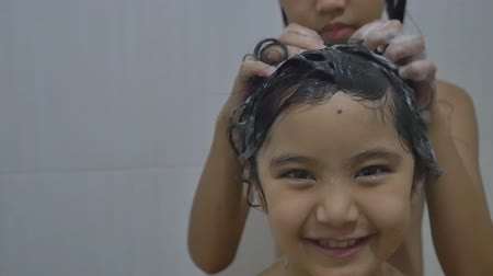 капелька : Asian child washes her sister hair in bathroom