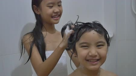 купаться : Asian child washes her sister hair in bathroom