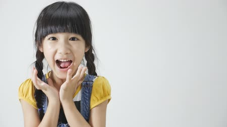 vay : Little Asian girl is surprised on white background Stok Video