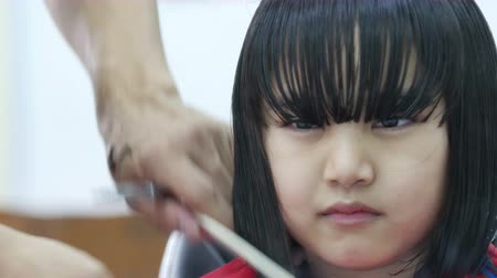 grzebień : Little Asian girl getting haircut in hair salon : 4K Video Wideo