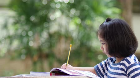 write : Little Asian girl doing homework in the garden at home Stock Footage