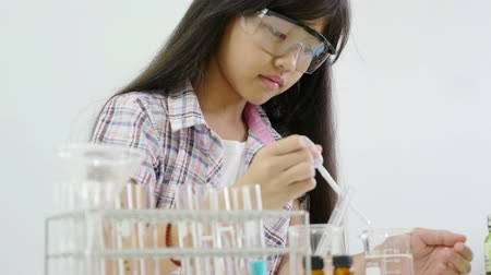 maior : Little Asian student girl making science experiments