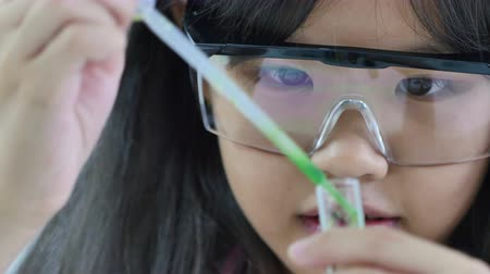 kísérlet : Little Asian student girl making science experiments. Education, Close up shot Stock mozgókép