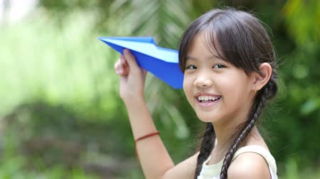 paper airplane : 4K of little Asian child playing with paper airplane in the park