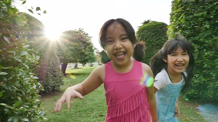 little : Asian sisters running around in the park and laughing together, Slow motion shot