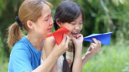 país : little Asian child playing paper airplane with mother in the park together Vídeos