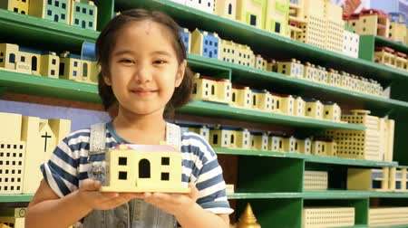 zabawka : Little Asian child showing wooden toy house Wideo