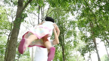 деревья : Asian father spinning happy girl daughter child around in park, Slow motion. Стоковые видеозаписи