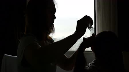 braid hairs : Silhouette Asian mother braids her daughters hair