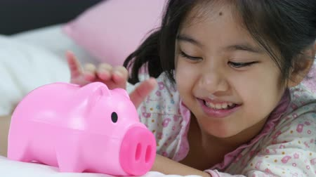kumbara : Happy Asian girl saving money in piggy bank