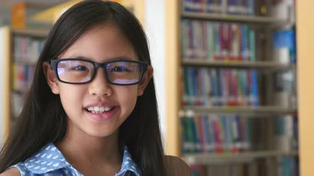 livro : 4K : Little Asian students reading a book in library, Tilt up shot