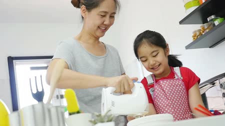 culinária : Happy Asian mother baking cookie with little daughter in apron, Pan shot