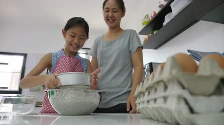 mutfak malzemesi : Happy Asian mother baking cookie with little daughter in apron, Pan shot