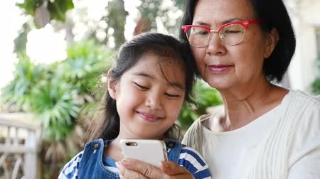 asian family : Little Asian girl using smart phone with her grandmother, Happy family concept, Slow motion shot.