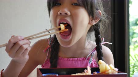 comida japonesa : Asian girl eating Japanese food sushi in a restaurant, Sushi is a traditional food of Japan Vídeos