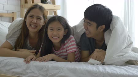 asian family : 4K : Happy Asian family, Daughter playing hide and seek with parents on the bed