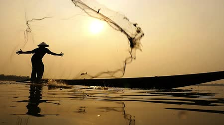 fishermen : Silhouette of traditional fishermen throwing net fishing in the lake at sunrise time Stock Footage