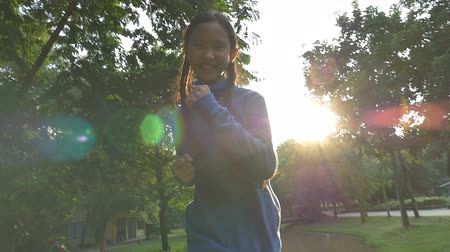sport dzieci : Slow motion shot : Happy Asian little girl running in the park with sunlight